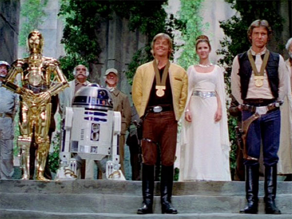 C-3PO (Anthony Daniels), R2-D2 (Kenny Baker), Luke Skywalker (Mark Hamill), Princess Leia (Carrie Fisher), Han Solo (Harrison Ford) and others celebrate destruction of the Death Star in STAR WARS (1977)